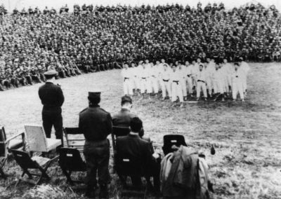 Supreme Master Kim Bok Man leads a demonstration of Taekwon-Do for members of the National Armed Forces in Korea, 1958. Captain Nam Tae Hi, standing at the microphone, directs the demonstration from the stage.