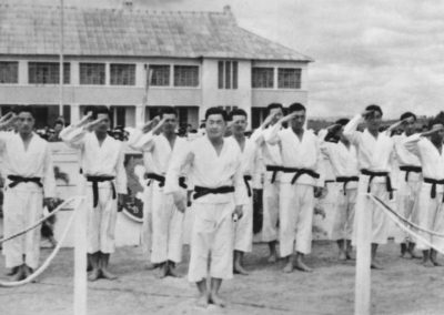 Master Sergeant Kim Bok Man (first row, second from right) and members of the historic first Korean National Armed Forces Taekwon-Do Demonstration Team salute before a demonstration in Vietnam, March, 1959. Captain Nam Tae Hi (center) commands the team. Also pictured are (first row, left to right) General Woo Jong Lim and Sergeant First Class Han Cha Kyo.
