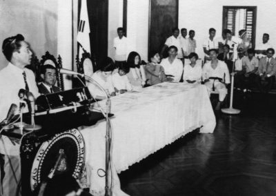 President Ferdinand Marcos of the Philippines speaks after a Taekwon-Do demonstration at Malacañang Palace, the official residence of the President, on August 15, 1970. Supreme Master Kim Bok Man and Bong Suk Kun, in doboks, are seated at the far end of the table.