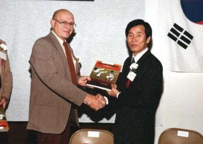 Supreme Master Kim Bok Man presents a copy of his book Practical Taekwon-Do: Defenses Against Weapons to an official of the city of O'Fallon, Missouri, at the 3rd Grand Opening Celebration for the Missouri Taekwon-Do Association in St. Louis, Missouri, U.S.A., 1983.
