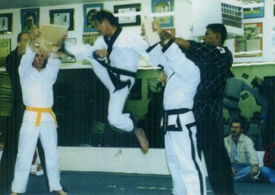 "Supreme Master Kim Bok Man breaks two 1"" boards with a jumping two direction twisting kick during a demonstration at the Taekwon-Do Grand Opening Celebration in Federal Heights, Colorado, U.S.A., 1995. Supreme Master Kim was 60 years old when this photograph was taken. Some of Supreme Master Kim's many photographs and newspaper clippings are displayed on the wall behind him."