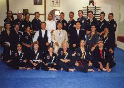 Supreme Master Kim Bok Man (2nd row, fifth from left), Master Kim Won Kuk (2nd row, fourth from left), Master Kim In Ki (2nd row, sixth from left) and Master Daniel Gaul (3rd row, fifth from left) pose with black belts of the World Jungyae Moosul Federation in Seattle, Washington, U.S.A., 1996.