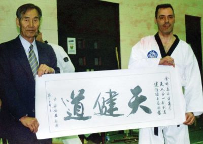 Supreme Master Kim Bok Man, President of the World Chun Kuhn Do Federation, presents a Chun Kuhn Do pennant to Master Andy Davies in the United Kingdom, November 16, 2002.