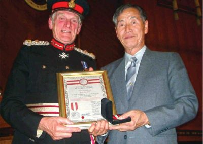 Supreme Master Kim Bok Man, recipient of the Flavian Medal of Merit for his lifelong commitment to teaching and promoting Taekwondo and the martial arts, poses with Her Majesty's Lord Lieutenant of Gloucestershire, Sir Henry Elwes, in the United Kingdom, November 14, 2003. (Photo courtesy of Master Andrew Davies.)