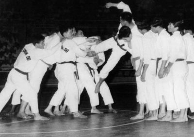 "Supreme Master Kim Bok Man breaks 3 pieces of 1"" board with a flying side kick over the shoulders of four men during a Taekwon-Do demonstration at Stadium Negara in Kuala Lumpur, Malaysia, July 1963. This historic demonstration was the first such demonstration of Taekwon-Do in Malaysia. Stadium Negara, which opened in April 1962, was the first indoor stadium in Malaysia."