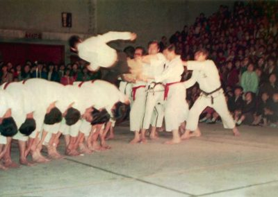 "Supreme Master Kim Bok Man breaks three pieces of 1"" board with a flying side kick over seven men during a Taekwon-Do demonstration at Hong Kong Stadium in Hong Kong, 1967."