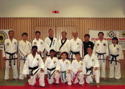 Supreme Master Kim Bok Man (back row, center) poses with instructors and organizers after the First Asian Chun Kuhn Taekwon-Do Seminar in Singapore, 2011. Also pictured are (standing from L-R) Master Don Looi, Master Dr. William Choo, Master Sam Looi, Master Brad Shipp, Grand Master Simon Lee, Master Johnny Yeo, Master Gary Tong, and Ms. Chau Ly.