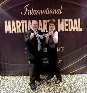Grandmaster Mike Swope poses with son Stephen Swope following his acceptance of Martial Arts Medal of Merit